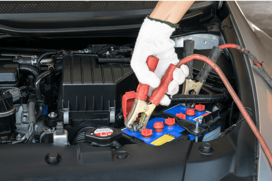 Car battery being jumpstarted by service operator
