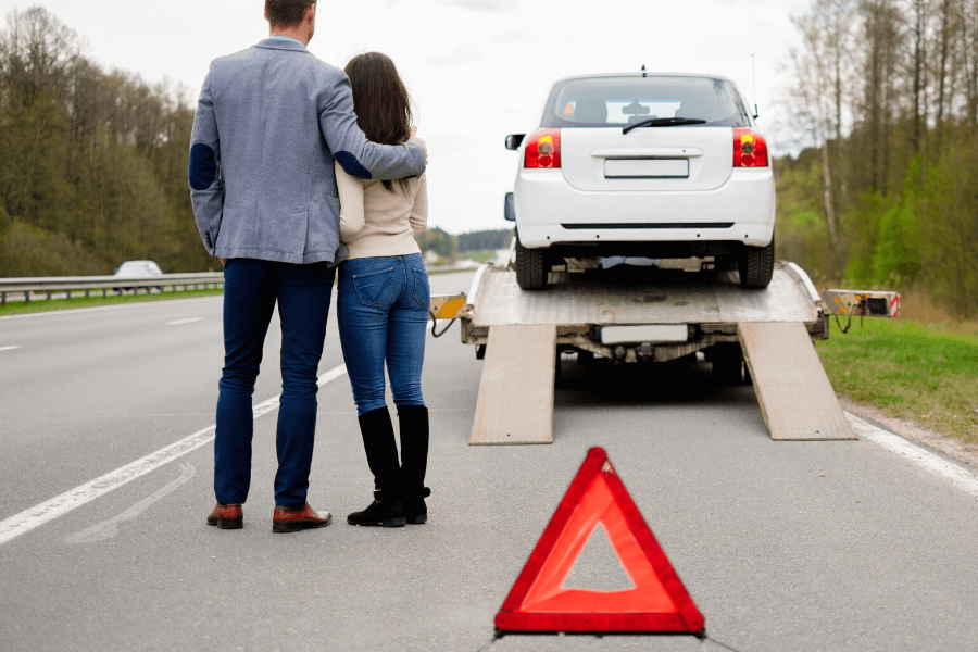 Couple standing on side of road having car towed