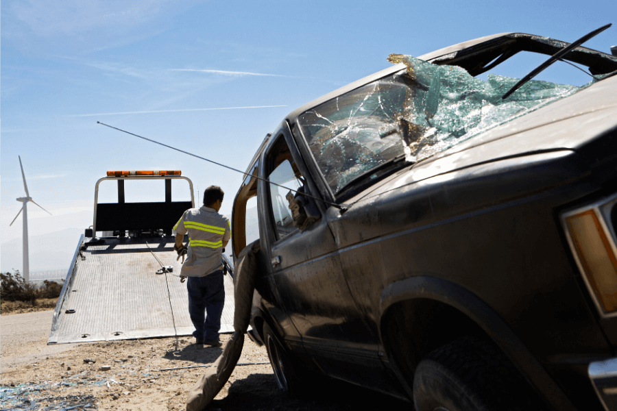 Tow truck flatbed wrecker service of totaled vehicle after accident