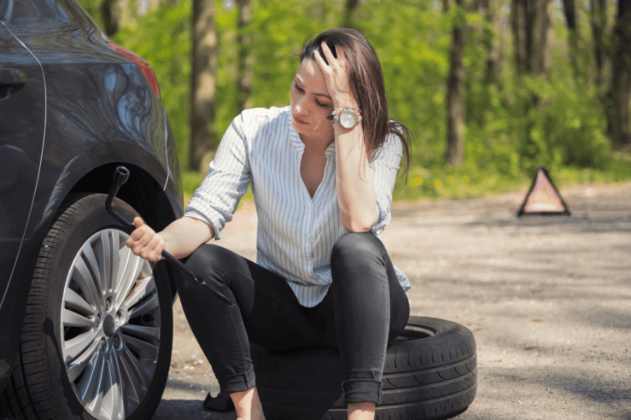 Woman on side of road with Flat Tire Kansas City, MO Towing