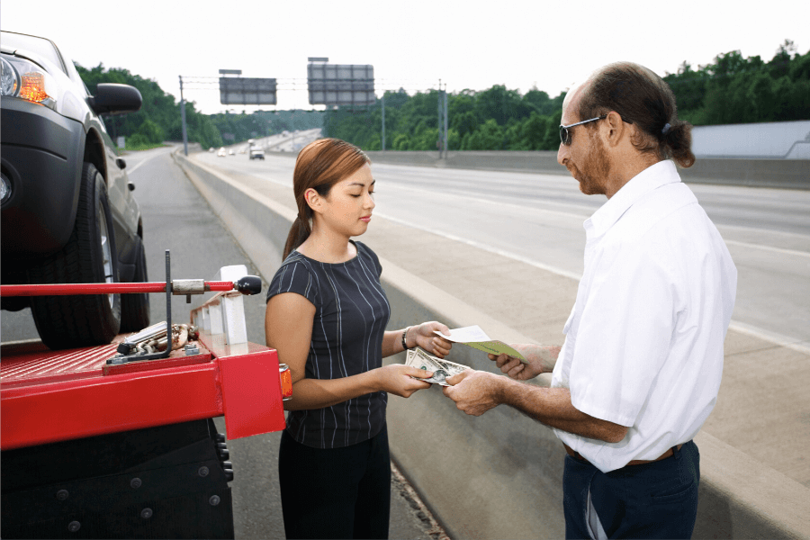 Woman standing on side of highway having car towed talking to tow truck driver